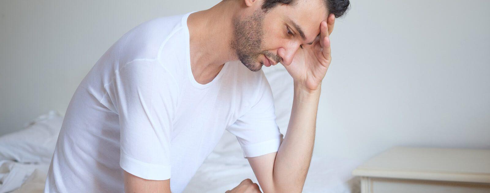 Mann sitzt besorgt auf der Bettkante, weil er an Erektionsstörungen leidet.