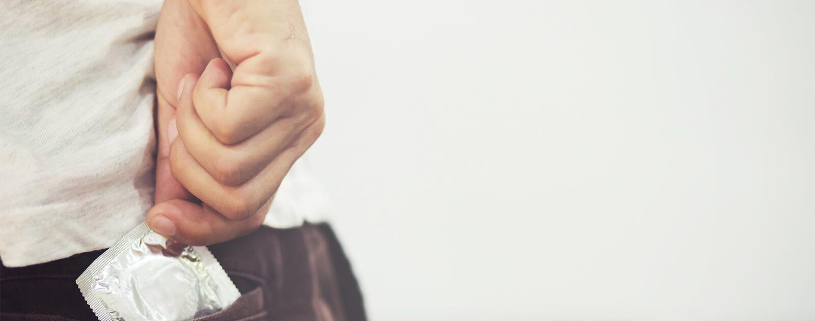 Mann, der ein Kondom aus der Tasche zieht, um sich vor Geschlechtskrankheiten zu schützen