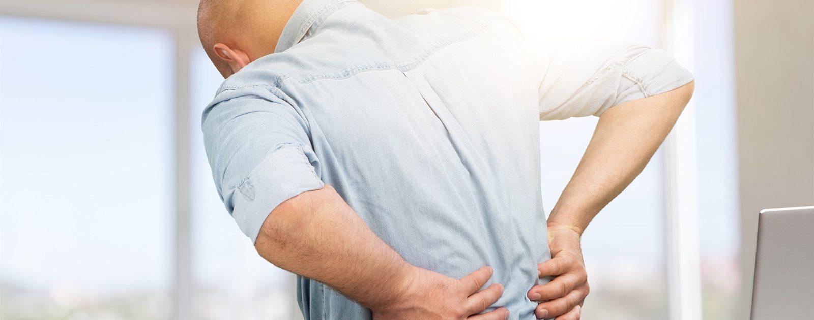 Ein Mann, der sich den Rücken hält, symbolisiert Nierenschmerzen aufgrund von Harnstau.