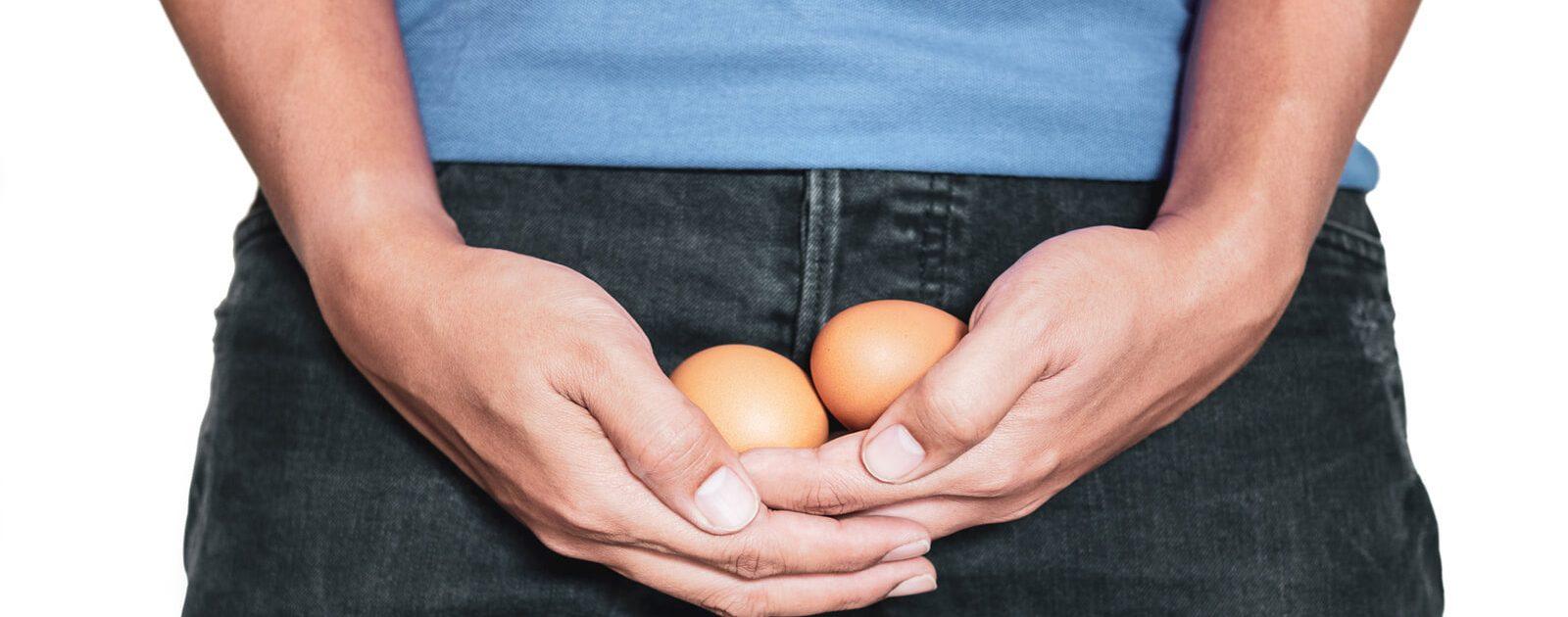 Mann, der zwei Eier hält, die symbolisch eine Hodentorsion darstellen.