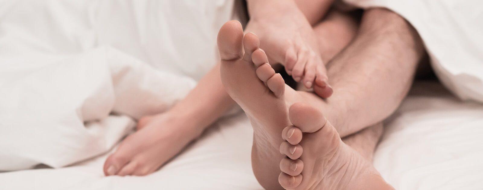 Nackte Beine unter der Bettdecke – ein Penisbruch gehört zu den typischen Sexunfällen.