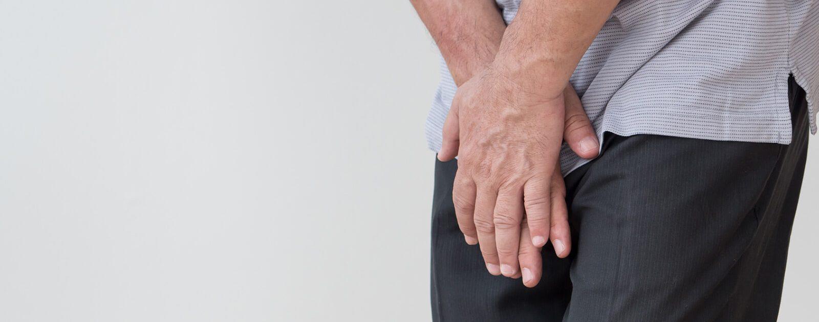Mann verdeckt seinen Schritt, da er an Inkontinenz leidet