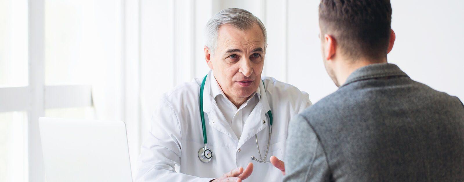 Urologe klärt männlichen Patienten über Risikofaktoren, Symptome und Diagnose von Blasenkrebs auf.