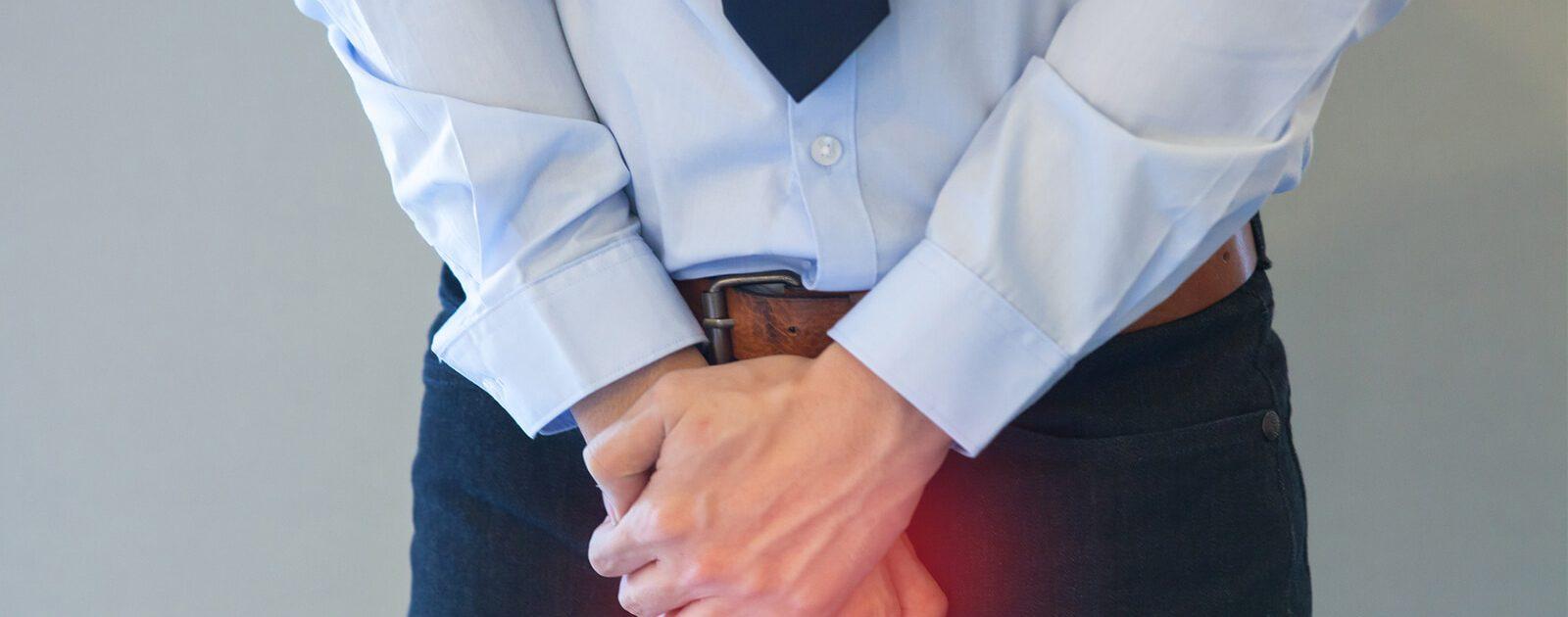 Mann drückt die Hände auf den Penis, da er eine schmerzhafte Harnröhrenentzündung hat.