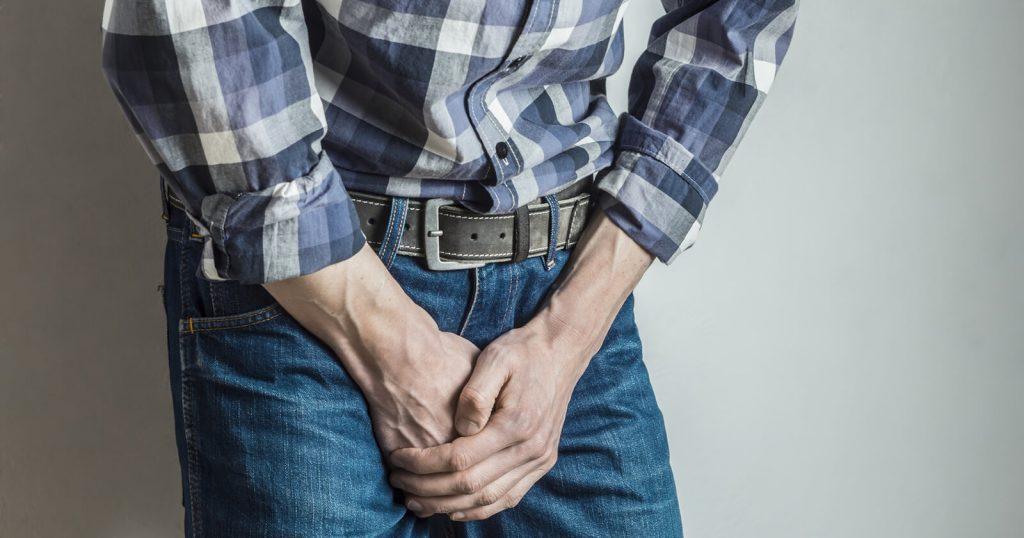 Mann hält sich die Hände vor der Blase, da er aufgrund seiner Reizblase plötzlich urinieren muss.