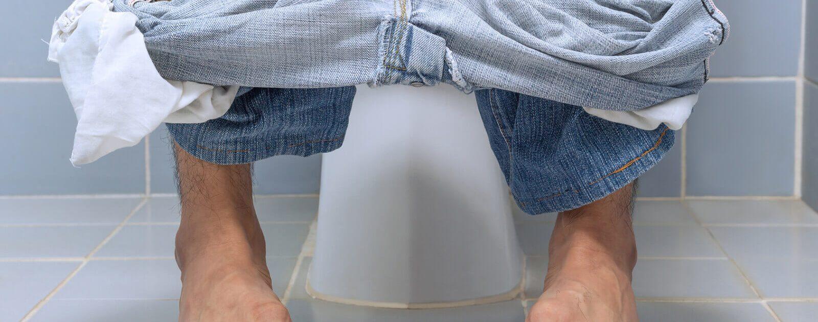 Mann auf Toilette leidet unter Schmerzen beim Wasserlassen