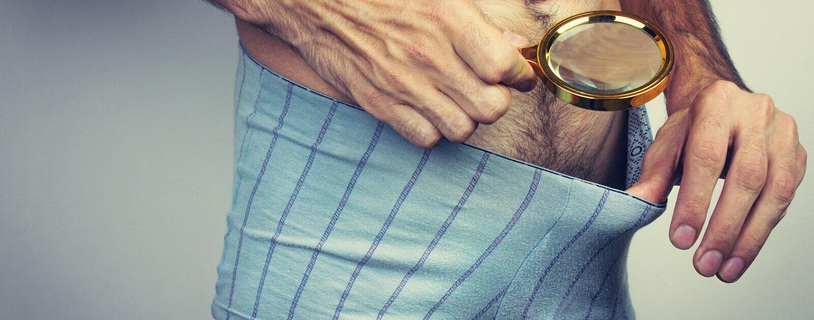 Mann untersucht seinen Penis mit einer Lupe, um eine Vorhautverengung feststellen zu können