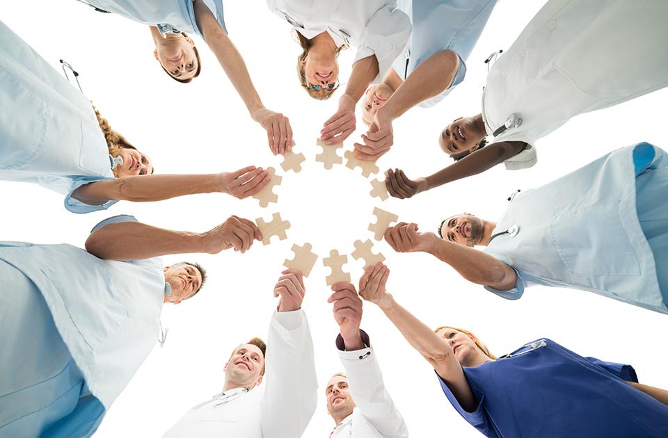 Team hält Puzzleteile zusammen; zur Veranschaulichung der Hilfe & Unterstützung bei Prostatakrebs